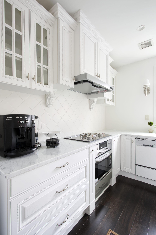 白いカップボードと、L型キッチンとアイランドキッチン