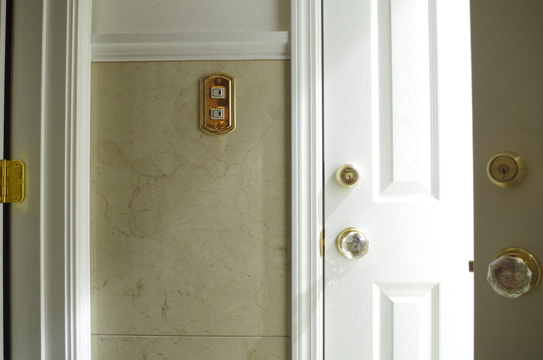 白いドアにガラスのノブハンドルと金色のスイッチプレート